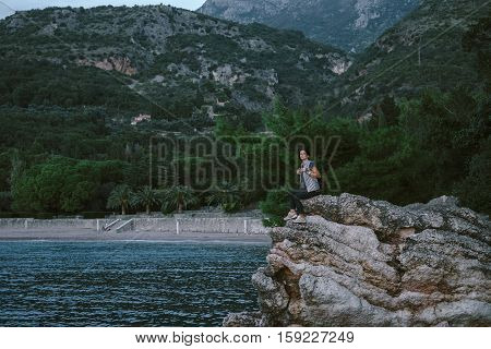 Happy Man and women sit down on a rock mountain in Montenegro freedom cocept