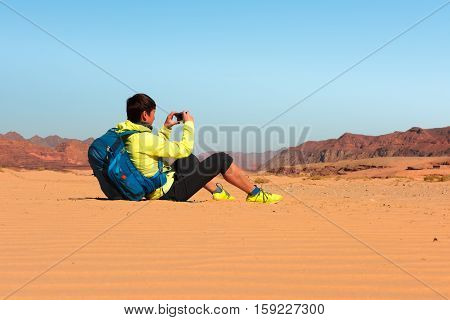 Woman mountain Hiker with backpack makes photo in Sinai desert