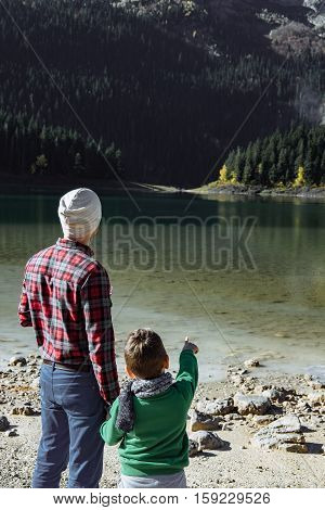Handsome Traveler With Son Looking At At The Black Lake, Montenegro
