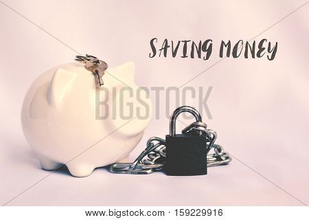 Close up a piggy bank with chain and key lock for save money.Selective and soft focus colour of vintage tone