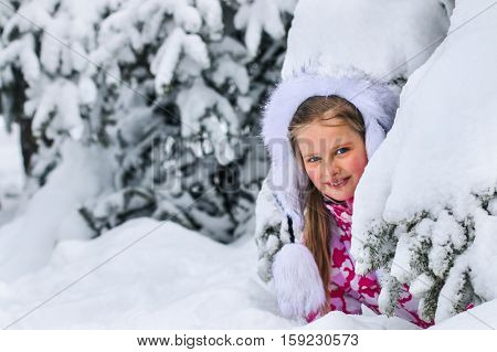 Portrait of little kid girl in winter clothes plying in deep snow uder fir tree.