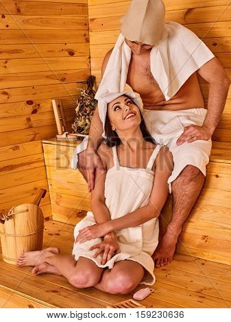 Loving couple relaxing in the sauna. Man tenderly embracing woman's shoulders. She looks at him lovingly.