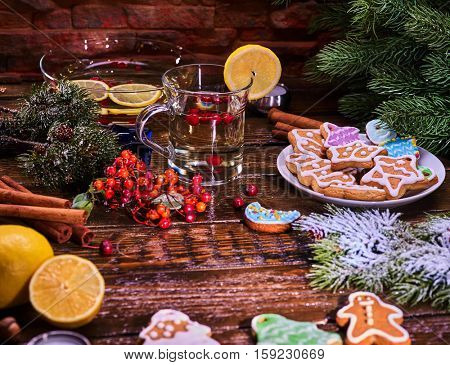 Christmas still life with mug decoration lemon slice hot punch from white whine on wooden table and gingerbread cookie. Lemon and fir branches on foreground.