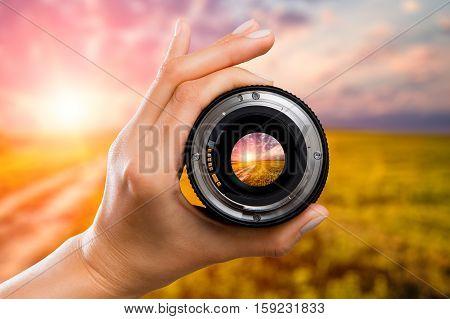 photography view camera photographer lens lense through field sunrise sunset sun sky cloud video photo digital glass hand blurred focus people concept - stock image