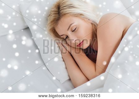 rest, comfort and people concept - young woman sleeping in bed at home over snow