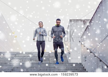 fitness, sport, exercising, people and healthy lifestyle concept - couple of sportsmen walking downstairs over snow