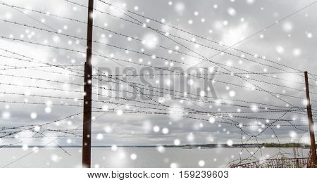 imprisonment and restriction concept - broken barb wire fence over gray sky and sea shore with snow