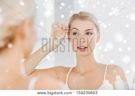 beauty and people concept - smiling young woman with tweezers tweezing eyebrow and looking to mirror at home bathroom over snow