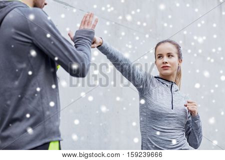 fitness, sport, martial arts, self-defense and people concept - woman with personal trainer working out strike outdoors over snow