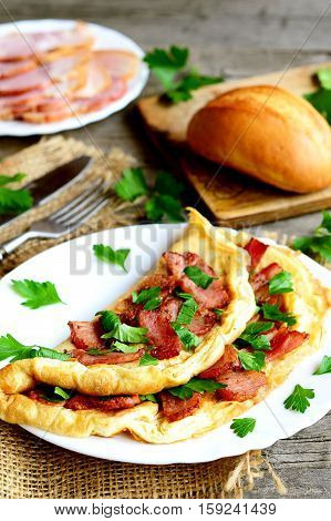 Homemade bacon omelette. Delicious omelette stuffed with bacon and parsley on a plate, bacon slices, bread, fork, knife, cutting board on old wooden table. Rustic style breakfast concept. Closeup