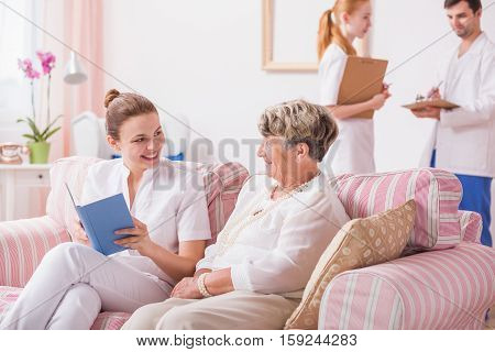 Caregiver Reading To Old Patient