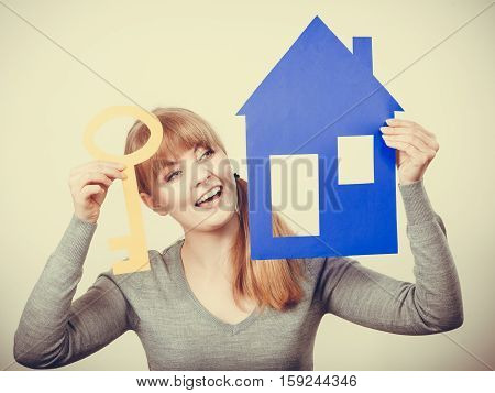 Security safety home ownership concept. Young blonde lady holding symbols. Cheerful girl showing house key cutouts.