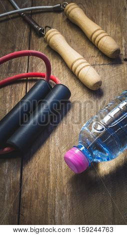 resistance band jump rope and water bottle on wooden block - vintage color style effect