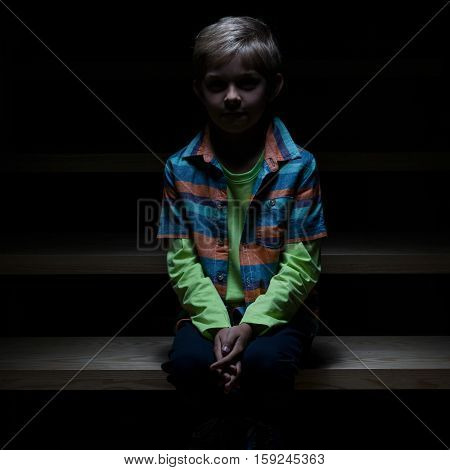 View of lonely boy sitting on staircase