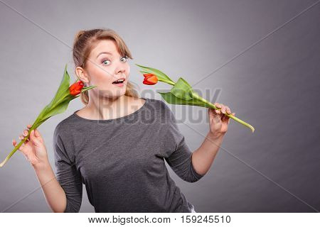Casual leisure beauty nature flora concept. Attractive lady dancing with flowers. Young lady waving two red tulips around.