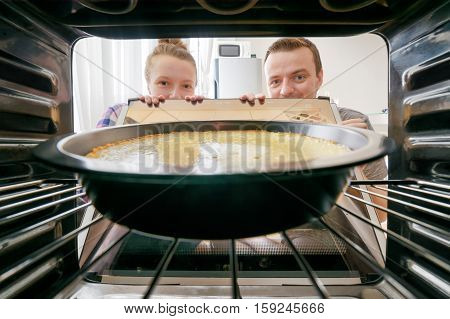 Young woman and young man looking at cheesecake into oven in kitchen. View from inside of the oven. Housewife and her husband holding the oven door.