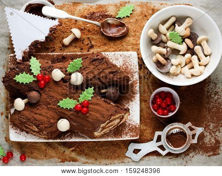 Traditional Christmas Yule Log cake decorated with chocolate holly mushrooms cookies