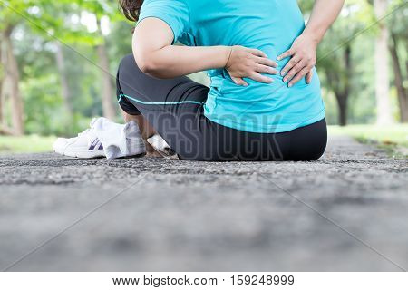 Sport injury. backache after exercise in the park