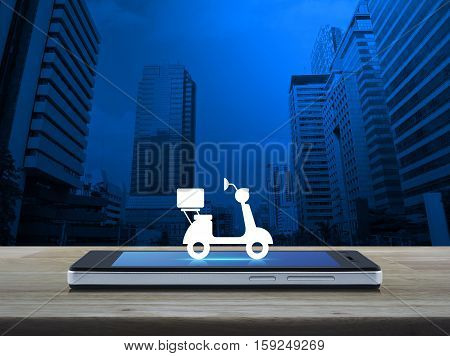 Motor bike icon on modern smart phone screen on wooden table over modern city tower Business delivery service concept