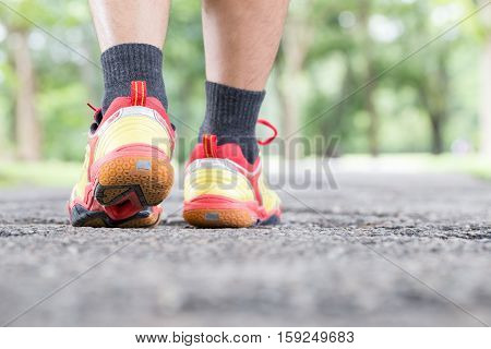 Leg of man walking on road at public park and closeup shoe. Sports healthy lifestyle concept