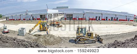 Zrenjanin Vojvodina Serbia - August 3 2015: Panorama is taken at construction site backhoe tractor is working on a construction site digging a pit.