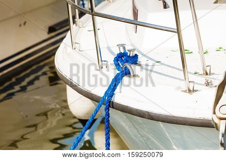 Sailing yachting security concept. Tied blue sailing rope on white boat outdoor shot