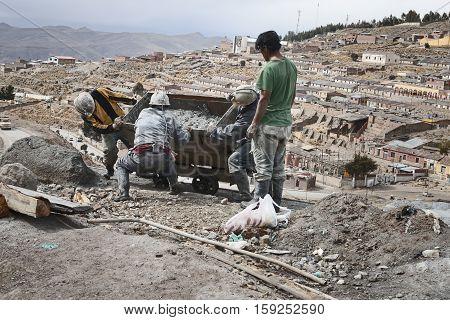 Miners emptying mine cart at Cerro Rico silver mine in Potosi. October 8, 2012 - Potosi, Bolivia