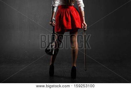 Female feet. A woman in a red skirt with a violin and fiddlestick