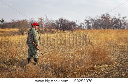 Hunter moving with shotgun looking for prey