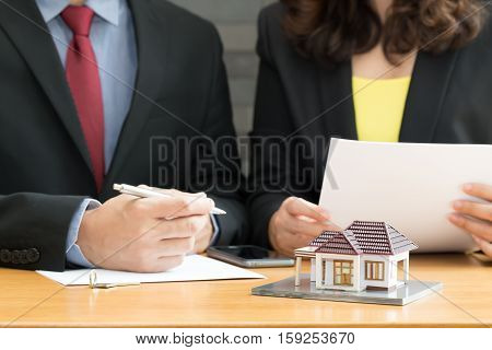 Businessman and businesswoman signing a contract for real estate investing