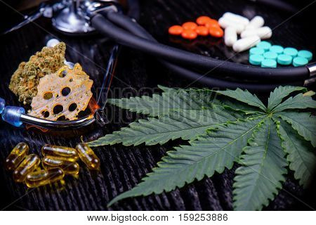 Medical marijuana products including cannabis leaf, dried bud, shatter piece, cbd caps and hash oil over black wood background