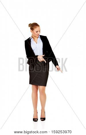 Young beautiful business woman pointing down