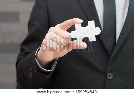 Businessman holding white jigsaw piece New vision concept