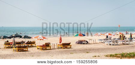 Arambol Goa India - December 08 2014: Tourists relax on the huge sandy beach of Arambol with sunbeds and sun umbrellas parasol on the Arabian Sea North Goa India