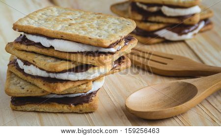 Smores placed on wooden table beside with wooden fork and spoon