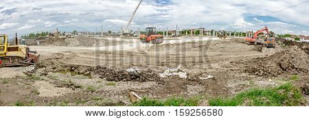 Panoramic landscape transform into urban area with machinery people are working. View on construction site.