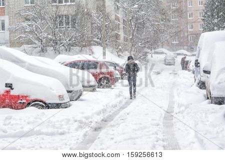 Snowstorm, snow-covered street and cars with a lonely pedestrian