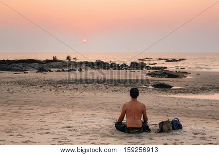 Morjim Goa India - December 08 2014: A man sitting in a yoga lotus position on a sandy beach of the sea and watch the sunset. Philosophical relaxing the concept of traveling and meditating.