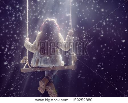 Happy child girl playing on a snowy winter walk. Little girl enjoys the game. Child girl playing on swing outdoors in snow. Outdoor fun for winter vacation. Portrait kid on dark background.