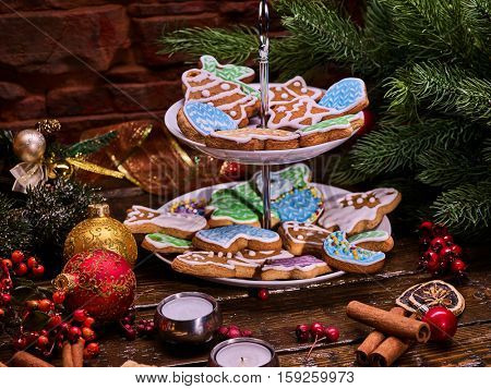 Christmas gingerbread cookies on Tiered Cookie Stand. Wooden table and cinnamon sticks . Christmas tree background.
