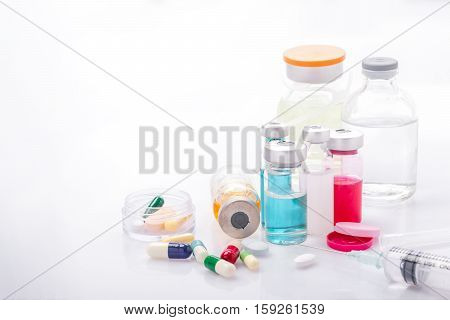 Glass Medicine Vials with syringe pills capsule on white table
