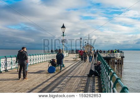 Penarth Wales United Kingdom - November 20 2016: On a cold sunny winter day a photo shoot is taking place on Penarth Pier while anglers are fishing and people are enjoying a walk as rain clouds are accumulating.