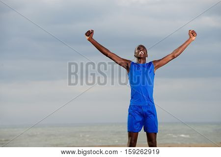 Young Sportsman On The Beach Celebrating Success