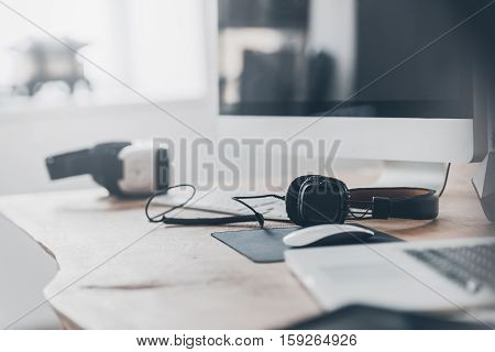 New innovations. Headphones and VR headset laying on the office desk and near laptop and computer