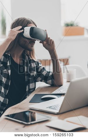 Innovation in business. Handsome young man with long hair adjusting his VR headset while sitting at his desk in creative office