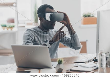 Virtual work. Handsome young African man in VR headset pointing in the air while sitting at the desk in creative office