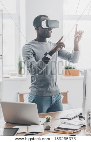 Fun with virtual reality headset. Handsome young African man in VR headset gesturing and smiling while standing in creative office