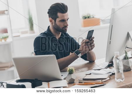 Texting am important message. Handsome young man typing a message with a serious face while sitting at the desk in creative office