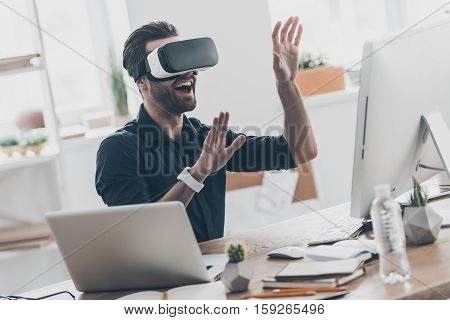 Future is now. Handsome young man in VR headset gesturing and smiling while sitting in creative office