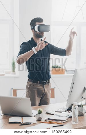 New reality is here! Handsome young man in VR headset gesturing while standing in creative office